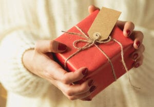 Close-up of woman holding gift packed in red paper