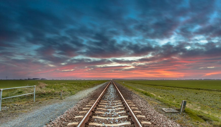 Dissapearing railroad on the horizon under a blue and red sky as a concept for future successfullness.