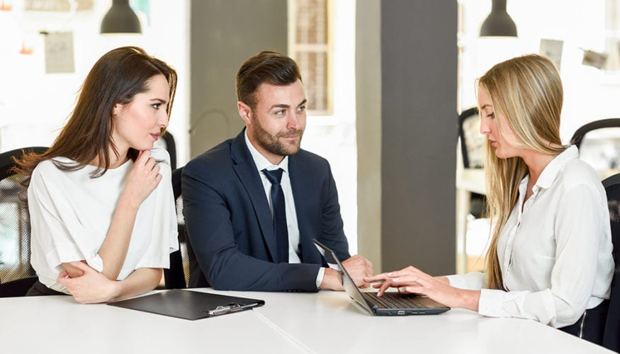 Blonde businesswoman explaining with laptop to smiling couple