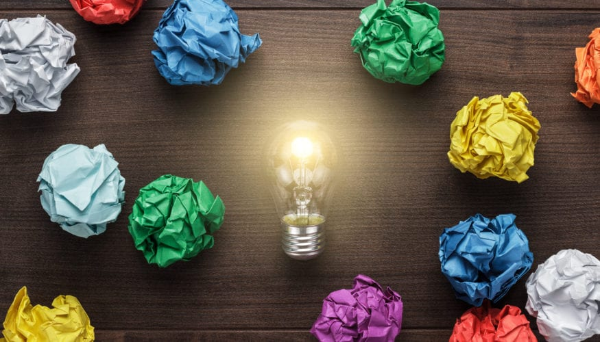 best idea concept with crumpled colorful paper and light bulb on wooden table