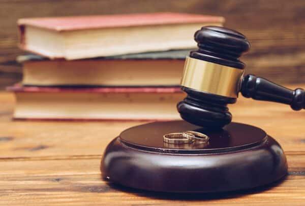 Wooden judge gavel and golden rings, divorce concept