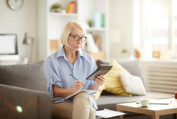 Portrait of modern senior woman calculating finances and budget while preparing tax report at home, copy space