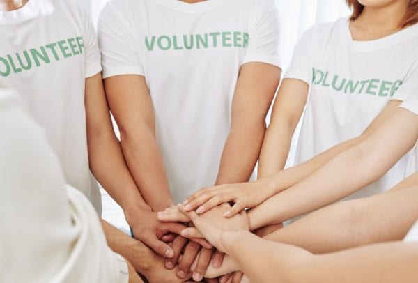 Group of volunteers stacking hands to support each other and express common girl