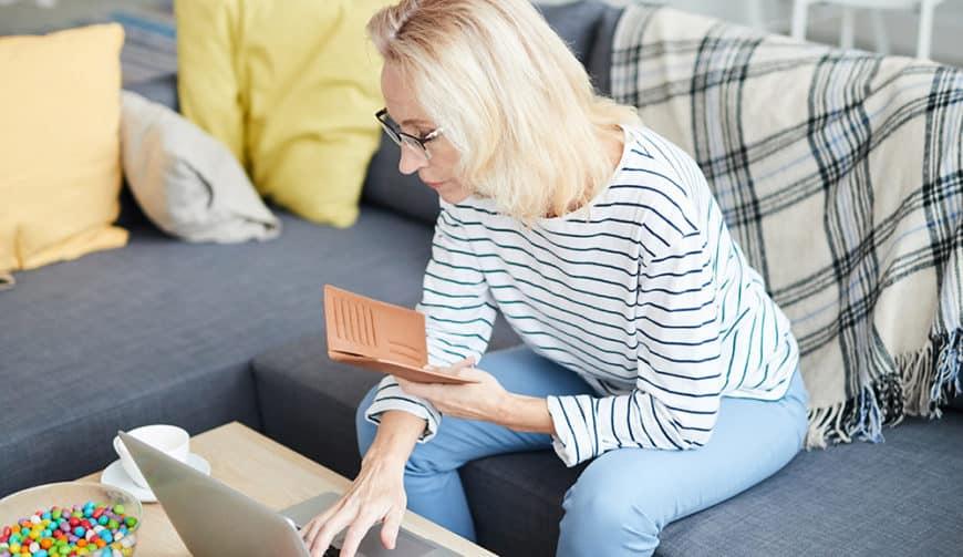 adult woman paying bills on laptop