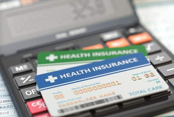 Medical insurance cards on the calculator. Health care costs concept. 3d illustration