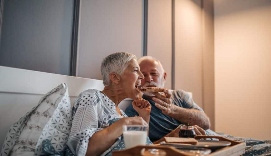 Elderly couple sharing breakfast in bed