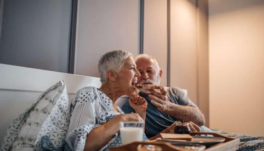 Elderly couple sharing breakfast in bed